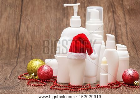 Christmas skincare cosmetics. Various cosmetic products for face and body care with Santa hat on wooden surface. Copy space. Christmas sale or gift concept