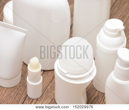 Various cosmetic products for face and body care on wooden surface. Daily skincare cosmetics. Top view, shallow depth of field
