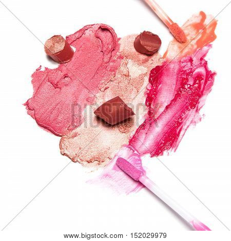 Different color samples of smeared and sliced lipstick, lip gloss with makeup brushes on white textured surface