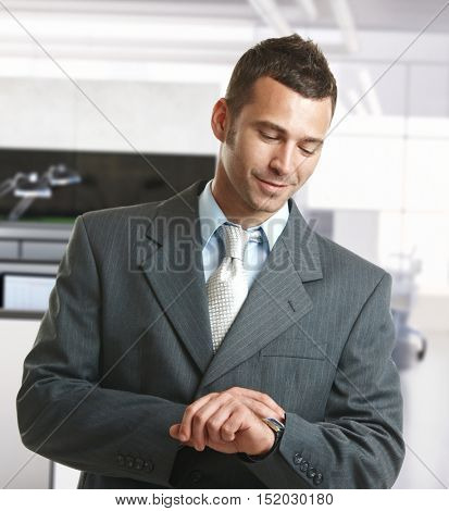 Businessman checking time in office, smiling.