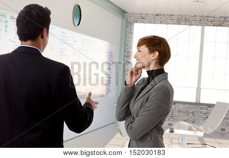 Businessman explaining plan to businesswoman at whiteboard.