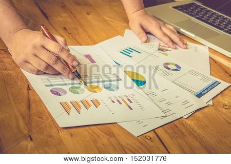 Business man pen pointing stock chart and partner working at the office. analysis document and using laptop. vintage effect.