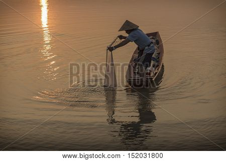 Fishermen fishing at sunset in the river.