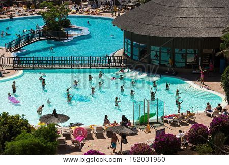 FUERTEVENTURA, SPAIN - SEPTEMBER 19, 2015: Active group of people a workout at the swimming pool on Fuertevetura. Spain