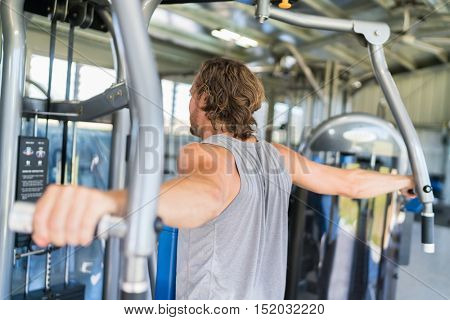 Man from behind training at fitness gym. Man doing workout on fitness machine at gym. Gym trainer athlete working out back muscles doing strength training exercises on gym  equipment.