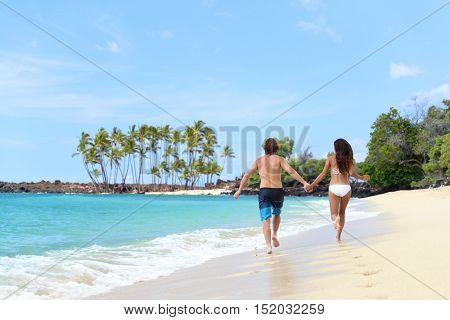 Happy couple from behind holding hands running having fun on tropical beach vacation. Hero view of people walking together in the splashing waves happy on summer holidays.
