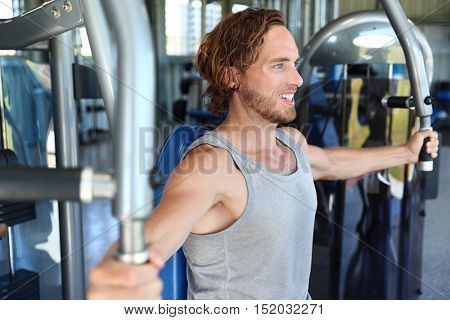 poster of Man at fitness gym. Man doing workout on fitness machine at gym. Gym trainer athlete working out che