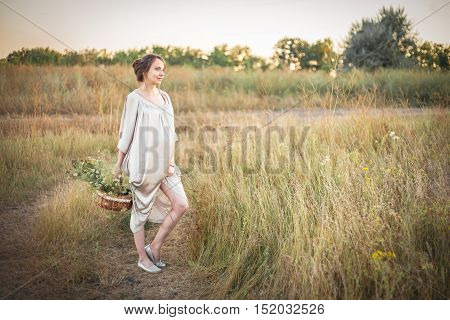 Young beautiful pregnant woman on a walk with wild flowers in her hands