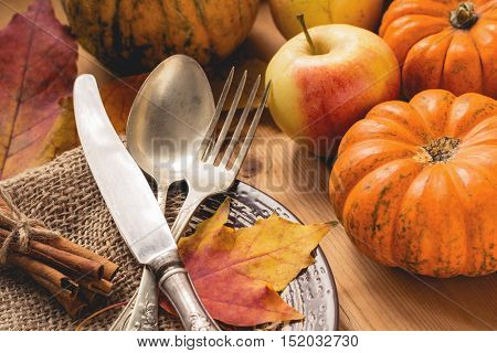 Thanksgiving table setting: pumpkins, apples, cinnamon sticks, fallen leaves and tableware on a plate.