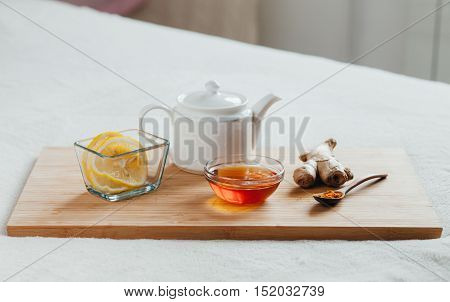 Herbal tea with chamomile flowers, turmeric and honey on a wooden board. Treatment of hot drink with ginger. Treatment of folk remedies in bed.