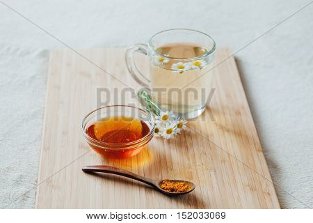 Herbal tea in glass cup with flowers of chamomile, turmeric and honey on a wooden board. Treatment of hot drink. Treatment of folk remedies in bed.