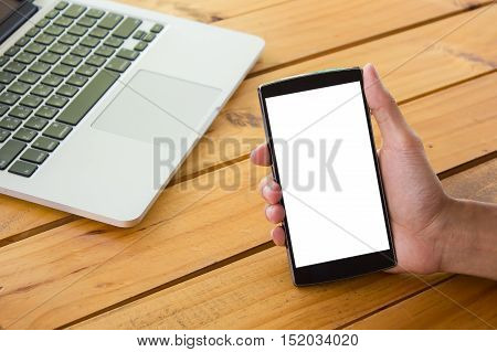 Closeup hand holding smart phone with blank and laptop.Smart phone with blank screen and can be add your texts or others on smart phone.