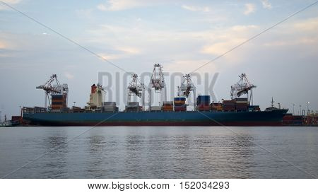 Container Cargo freight ship with working crane bridge in shipyard at dusk for Logistic Import Export background select focus