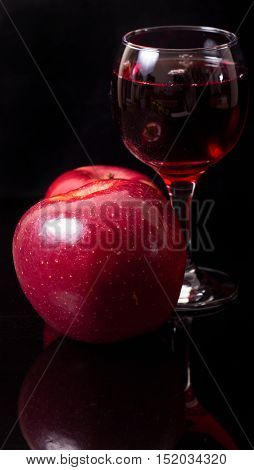 Apples and glass of wine on a black background. Red apples and red wine in a glass glass on the black reflecting background. Vertical shot