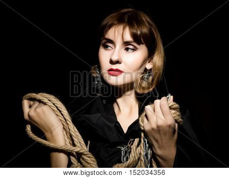 mysterious young woman holding rope. on a dark background.