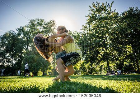 Couple dancing bachata in park backlit training dip figure