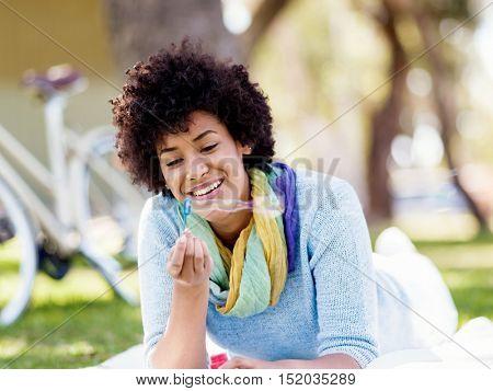 Beautiful woman blowing bubbles in park