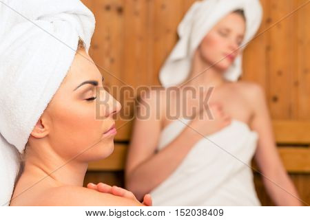 Two Women in wellness spa relaxing in wooden sauna