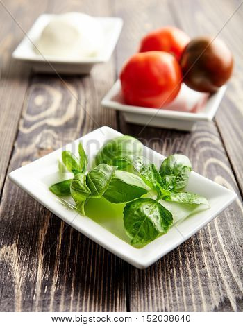 One of the main ingredients of Italian Caprese salad mozzarella cheese on white plate. Juicy tomatoes and fresh Basil behind. Traditional Mediterranean cuisine. Popular Italian dish on wooden table