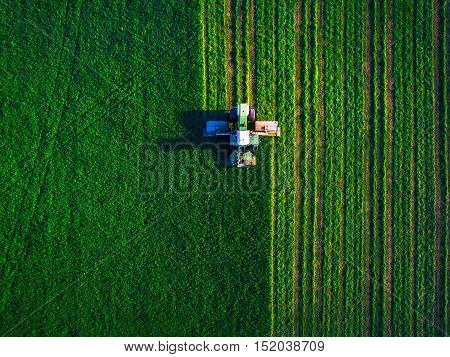 Tractor mowing green field, aerial view, agricultural concept