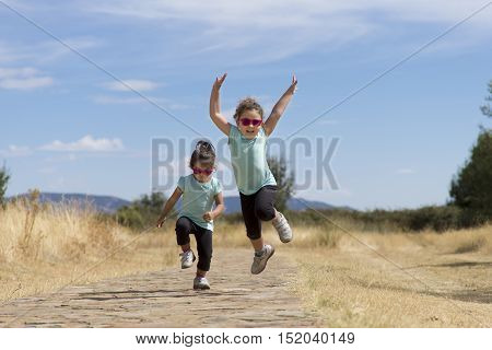 Portrait of little girls in similar wear jumping holding hand in hand along stone path in park.