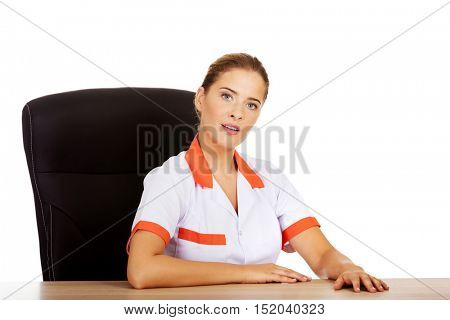 Female doctor or nurse sitting behind the desk