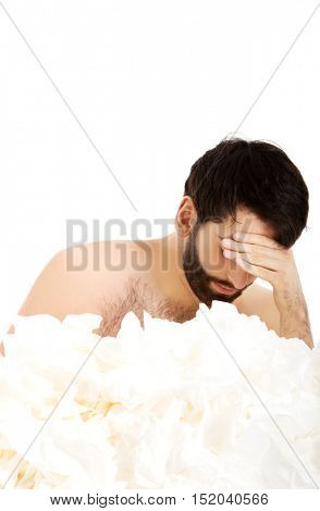Sick man sitting with a lot of tissues.
