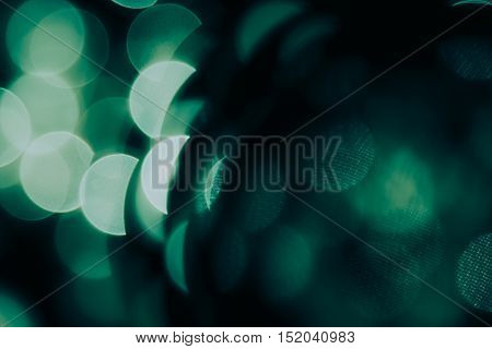 Bokeh dark green semicircles on black background. Abstract music background.