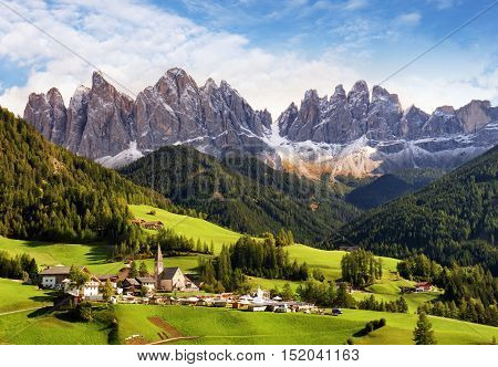 Val di Funes Trentino Alto Adige Italy. The great autumnal colors shines under the late sun with Odle on the background and Santa Magdalena Village on the foreground.