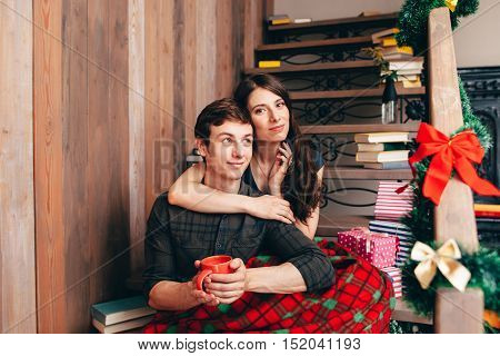 Woman hugs her boyfriend on wooden stairs at home. Happy couple having coffee break in Christmas decorating house, free space