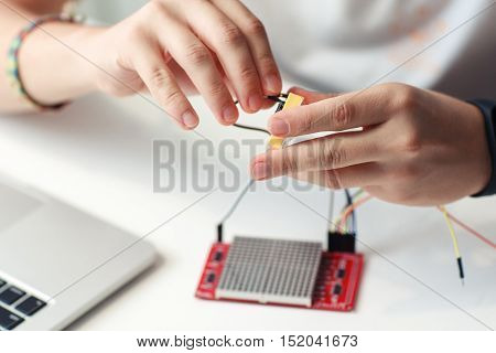 Engineer hands connecting electronic components. Close-up of master developing new device, blurred led matrix display