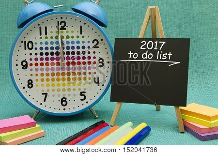 2017 New Year to do list written on colorful sticky notes pinned on cork board.