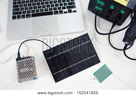 Solar battery connected to transmitter. Alternative energy resource. Engineer workplace, modern technology, electronic development, ecology concept