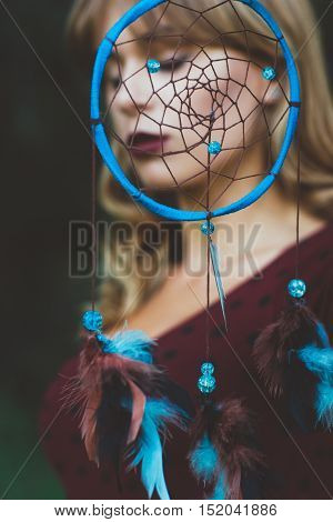 Beautiful woman portrait through dream catcher hoop. American Indian decoration element and gorgeous blonde in red dress. Luxury, art photography, beauty, soul concept