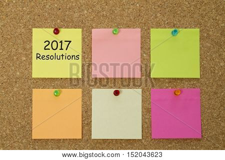 2017 New Year resolutions written on colorful sticky notes pinned on cork board.