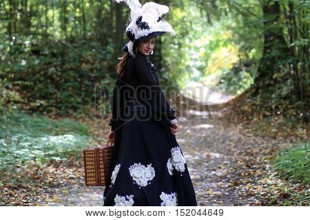 girl in retro dress 18th century with valise in the park