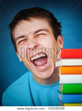 Happy Student with the Books on the Blue Background closeup