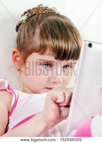 Small Girl with Tablet Computer on White Wall Background