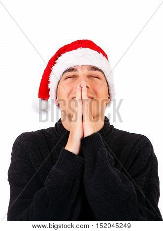 Young Man in Santa Hat Praying Isolated on the White Background
