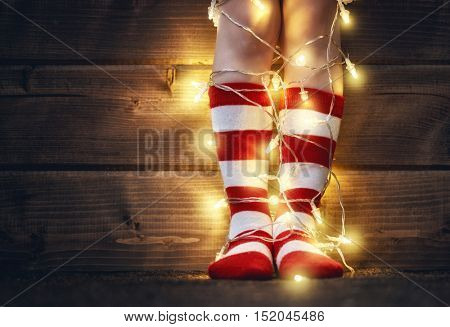 Merry Christmas and Happy Holiday! Baby feet in red and white socks with a festive garland on wooden background.