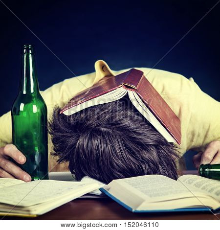 Toned Photo of Student with a Beer Bottle sleep on the Books