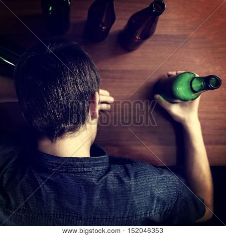 Toned Photo of Tired Man sleep with Bottle of the Beer on a Table