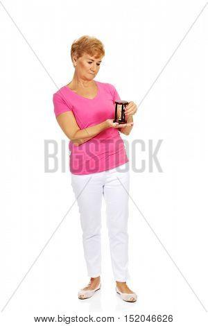 Smile senior woman holding sandglass
