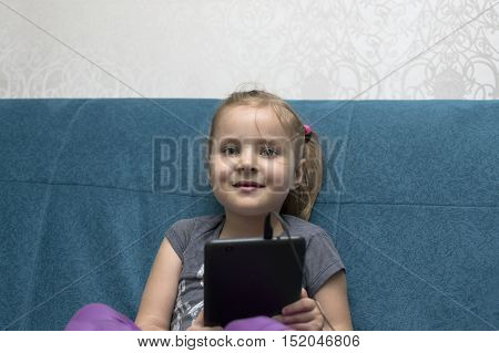 A liitle girl looking happy posing with a tablet sitting on a sofe indoors cropped portrait