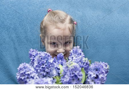 A young happy looking happy girl holding flowers studio portrait with selective focus