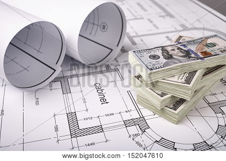 Construction of the building layout, construction financing, packs of dollars, building drawing on paper, drawings rolled in a roll