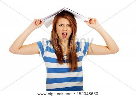 Screaming teenage woman with notebook on head