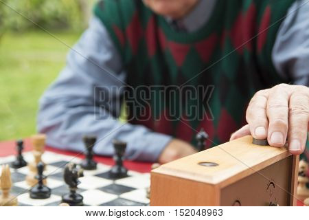 Mature man playing chess in old chessboard