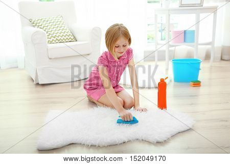 Small girl cleaning carpet on light background