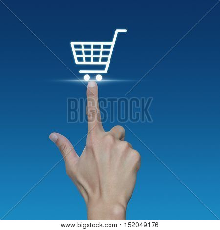 Hand pressing shopping cart icon over blue background Shopping online concept